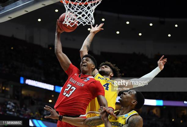Jarrett Culver of the Texas Tech Red Raiders drives to the basket against Charles Matthews and Isaiah Livers of the Michigan Wolverines during the...