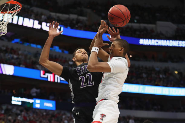 Jarrett Culver of the Texas Tech Red Raiders is blocked by TJ Holyfield of the Stephen F Austin Lumberjacks in the second half in the first round of...