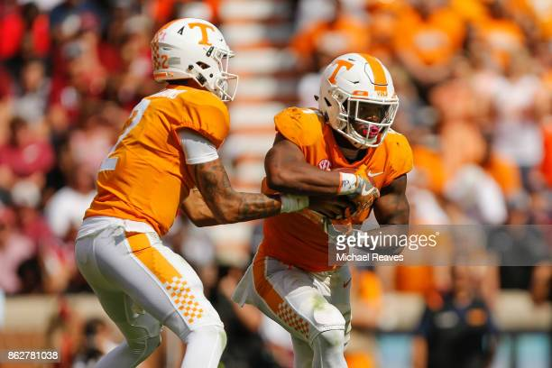 Jarrett Guarantano of the Tennessee Volunteers hands the ball off to John Kelly against the South Carolina Gamecocks at Neyland Stadium on October 14...