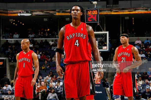 Jarrett Jack and Chris Bosh and Antoine Wright of the Toronto Raptors stand on the court during the game against the Memphis Grizzlies on October 30...