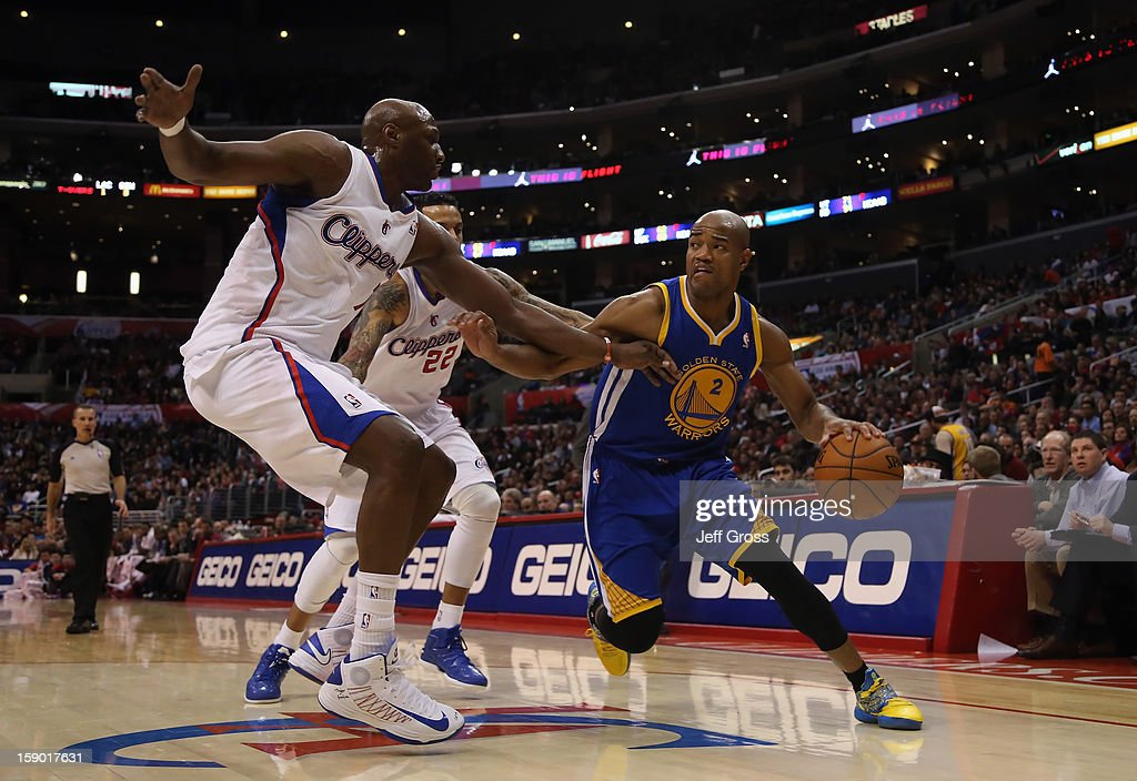 Jarrett Jack #2 of the Golden State Warriors is defended by Lamar Odom (L) #7 and Matt Barnes #22 of the Los Angeles Clippers in the first half at Staples Center on January 5, 2013 in Los Angeles, California.