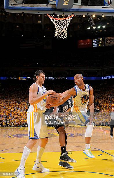 Jarrett Jack of the Golden State Warriors passes against Tim Duncan of the San Antonio Spurs to teammate Andrew Bogut in Game Four of the Western...