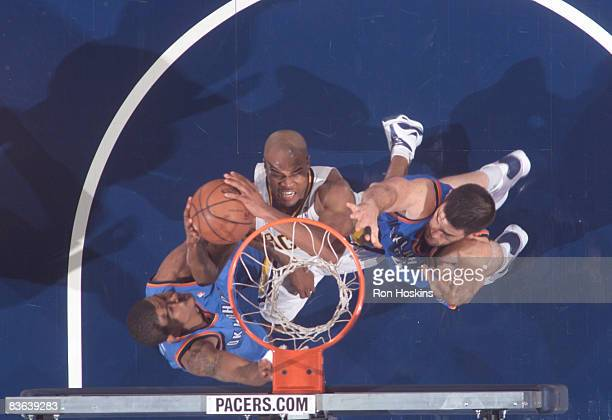 Jarrett Jack of the Indiana Pacers battles Earl Watson and Nick Collison of the Oklahoma City Thunder at Conseco Fieldhouse on November 10 2008 in...