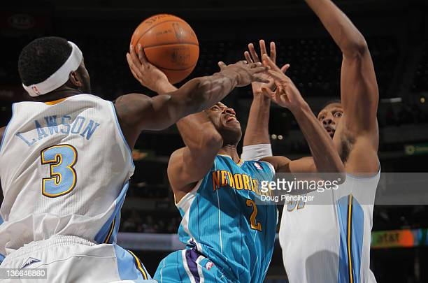 Jarrett Jack of the New Orleans Hornets tries to get off a shot against Ty Lawson of the Denver Nuggets and has it blocked by Nene Hilario of the...