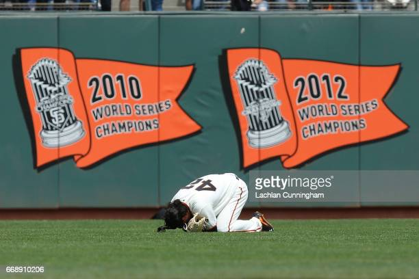 Jarrett Parker of the San Francisco Giants falls to the ground after making a catch against the outfield wall in the fourth inning against the...