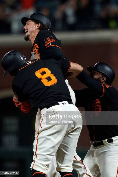 Jarrett Parker of the San Francisco Giants is congratulated by Hunter Pence and Denard Span after hitting a walk off single in the tenth inning...