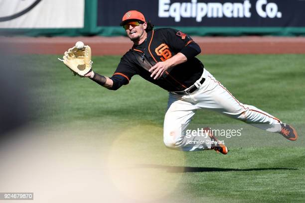 Jarrett Parker of the San Francisco Giants makes a diving catch in the fifth inning of the spring training game against the Kansas City Royals at...