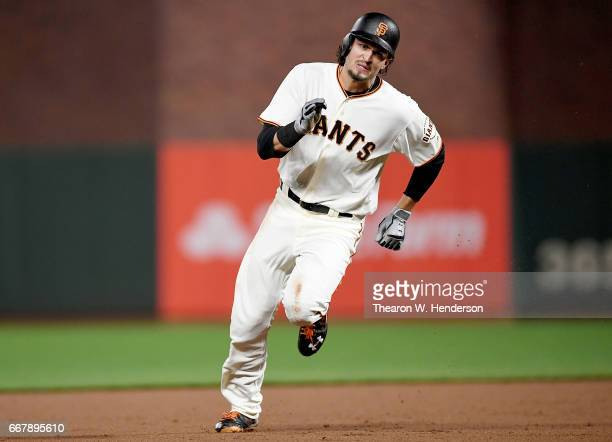 Jarrett Parker of the San Francisco Giants races into third base with a tworun triple against the Arizona Diamondbacks in the bottom of the seventh...