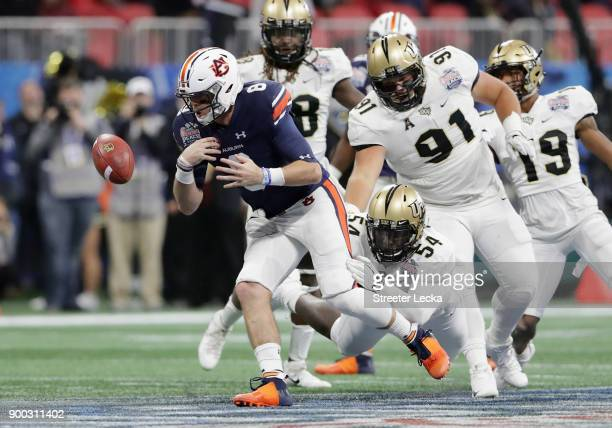 Jarrett Stidham of the Auburn Tigers fumbles the ball as he is tackled by AJ Wooten of the UCF Knights in the second quarter during the ChickfilA...