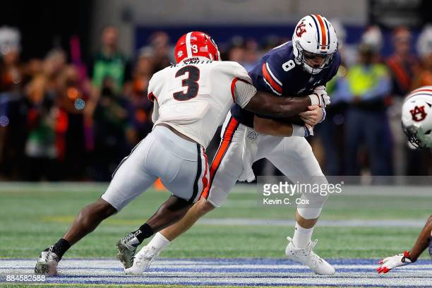 Jarrett Stidham of the Auburn Tigers is tackled by Roquan Smith of the Georgia Bulldogs during the first half in the SEC Championship at...