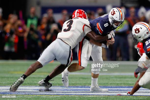 Jarrett Stidham of the Auburn Tigers is tackled by Roquan Smith of the Georgia Bulldogs during the first half in the SEC Championship at MercedesBenz...