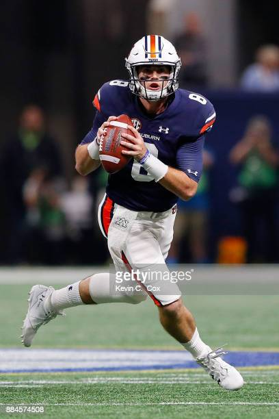 Jarrett Stidham of the Auburn Tigers rolls out on a pass play during the first half against the Georgia Bulldogs in the SEC Championship at...