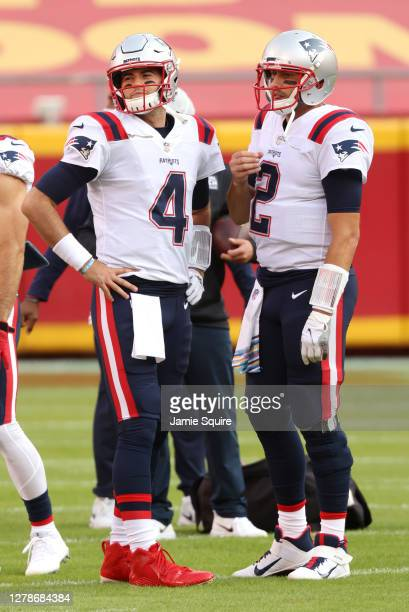 Jarrett Stidham of the New England Patriots and Brian Hoyer look on before the game against the Kansas City Chiefs at Arrowhead Stadium on October 05...