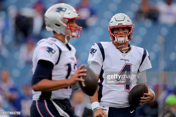 Jarrett Stidham of the New England Patriots looks on as Tom Brady warms up prior to the game against the Buffalo Bills at New Era Field on September...