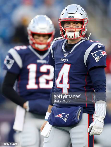 Jarrett Stidham of the New England Patriots looks on next to Tom Brady before the game against the Buffalo Bills at Gillette Stadium on December 21...