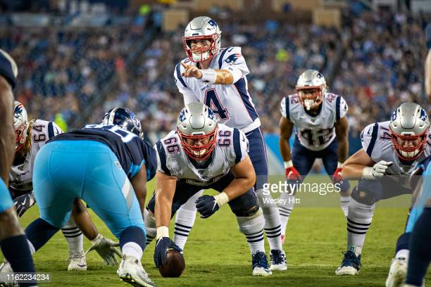 Jarrett Stidham of the New England Patriots points out the blocking assignment during a week two preseason game against the Tennessee Titans at...