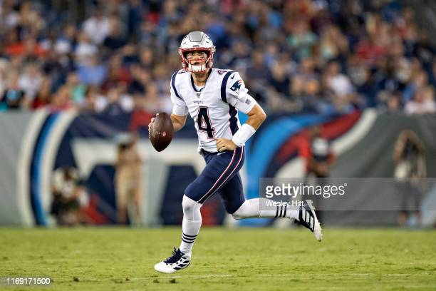 Jarrett Stidham of the New England Patriots rolls out to pass during a game against the Tennessee Titans during week two of the preseason at Nissan...