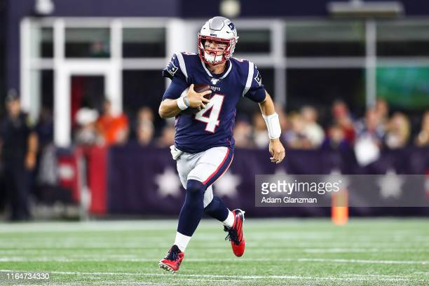 Jarrett Stidham of the New England Patriots runs with the ball during a preseason game against the New York Giants at Gillette Stadium on August 29...