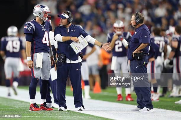 Jarrett Stidham of the New England Patriots talks with Offensive Coordinator Josh McDaniels and Head Coach Bill Belichick during the preseason game...