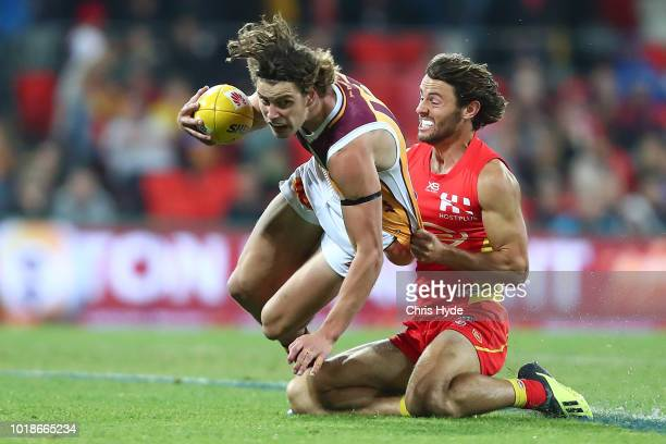 Jarrod Berry of the Lions is tackled by Lachie Weller of the Suns during the round 22 AFL match between the Gold Coast Suns and Brisbane Lions at...