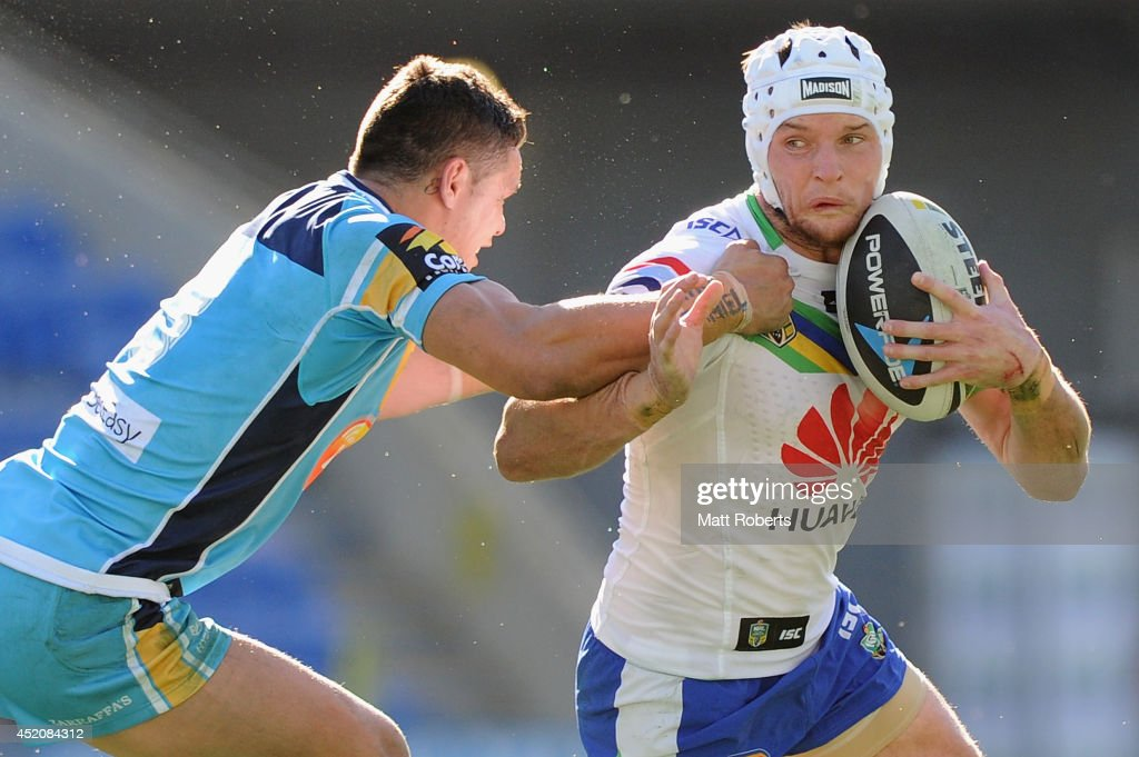 Jarrod Croker of the Raiders is tackled by James Roberts of the Titans during the round 18 NRL match between the Gold Coast Titans and the Canberra Raiders at Cbus Super Stadium on July 13, 2014 on the Gold Coast, Australia.