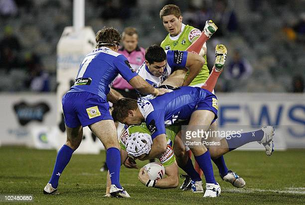 Jarrod Croker of the Raiders is tackled during the round 16 NRL match between the Canberra Raiders and the Canterbury Bulldogs at Canberra Stadium on...
