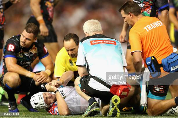 Jarrod Croker of the World All Stars lays on the ground injured attended to by a trainer during the NRL All Stars match between the 2017 Harvey...
