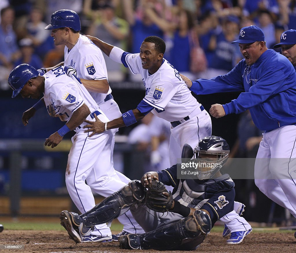 Jarrod Dyson #1 is congratulated by Mitch Maier #12, Alcides Escobar #2 and Billy Butler after scoring the game-winning run as Martin Maldonado #12 of the Milwaukee Brewers looks on during an interleague game at Kauffman Stadium on June 14, 2012 in Kansas City, Missouri. The Royals won 4-3.