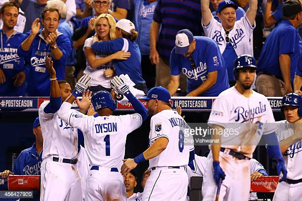 Jarrod Dyson of the Kansas City Royals celebrates with teammates after scoring on a sacrafice fly by Norichika Aoki in the ninth inning to tie the...