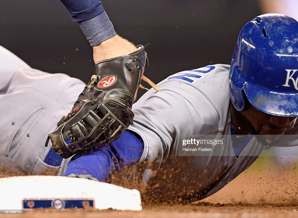 Jarrod Dyson #1 of the Kansas City Royals dives safely back to first base as Joe Mauer #7 of the Minnesota Twins applies the tag during the ninth inning of the game on October 2, 2015 at Target Field in Minneapolis, Minnesota. The Royals defeated the Twins 3-1.