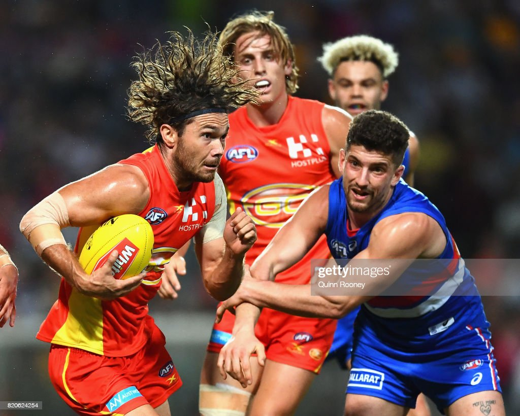 Jarrod Harbrow of the Suns breaks free of a tackle by Tom Liberatore of the Bulldogs during the round 18 AFL match between the Western Bulldogs and the Gold Coast Suns at Cazaly's Stadium on July 22, 2017 in Cairns, Australia.