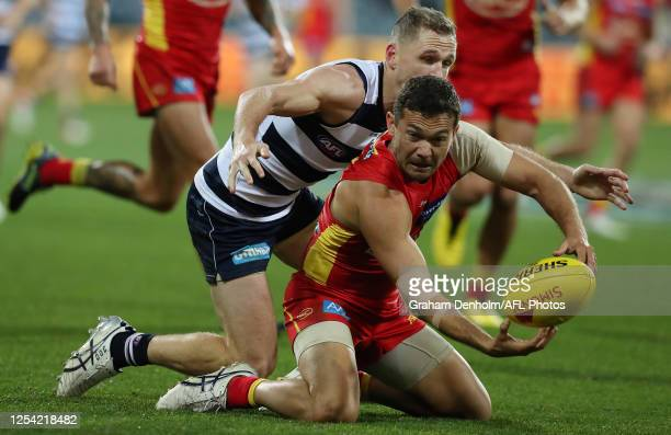 Jarrod Harbrow of the Suns handballs as he is tackled by Joel Selwood of the Cats during the round 5 AFL match between the Geelong Cats and the Gold...