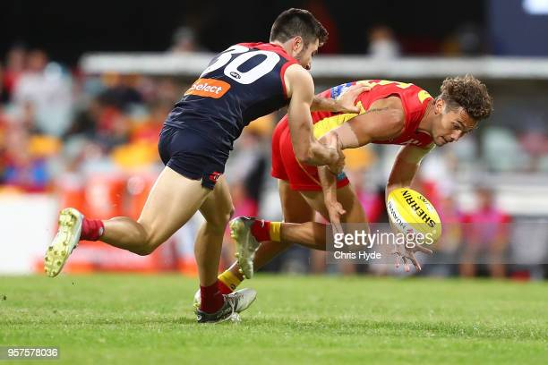 Jarrod Harbrow of the Suns is tackled by Alex NealBullen of the Demons during the round eight AFL match between the Gold Coast Suns and the Melbourne...