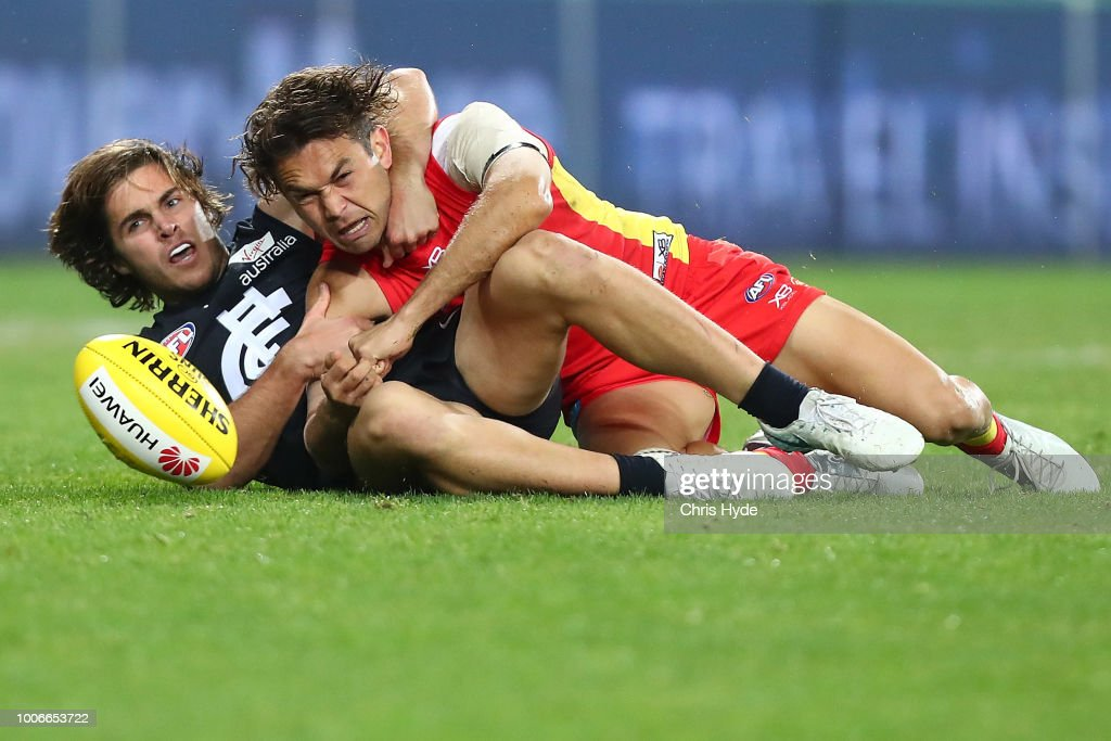 Jarrod Harbrow of the Suns is tackled by Cameron Polson of the Blues during the round 19 AFL match between the Gold Coast Suns and the Carlton Blues at Metricon Stadium on July 28, 2018 in Gold Coast, Australia.