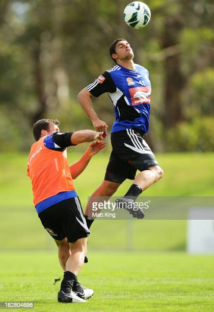 Jarrod Kyle heads the ball above Lucas Neill during a Sydney FC ALeague training session at Macquarie Uni on February 28 2013 in Sydney Australia