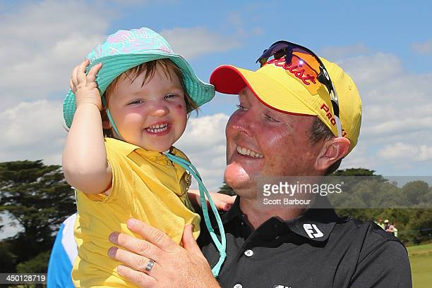Jarrod Lyle of Australia hugs his daughter Lusi after completing his round during round four of the 2013 Australian Masters at Royal Melbourne Golf...