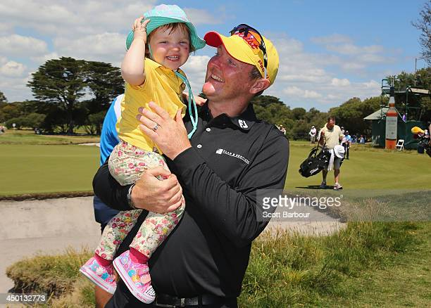 Jarrod Lyle of Australia hugs his daughter Lusi on the 18th green after completing his round during round four of the 2013 Australian Masters at...