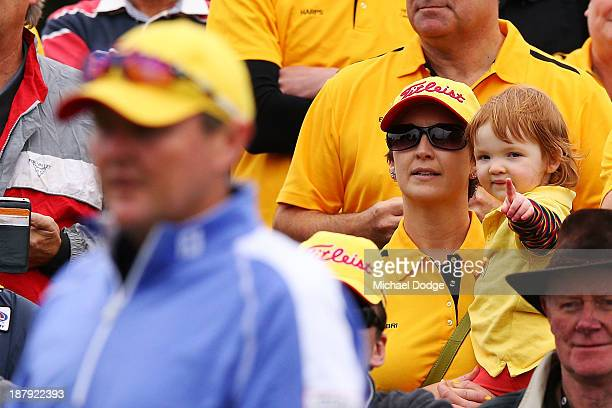 Jarrod Lyle of Australia is watched by his daughter Lusi Lyle and wife Briony Lyle before his shot on the first tee during round one of the 2013...