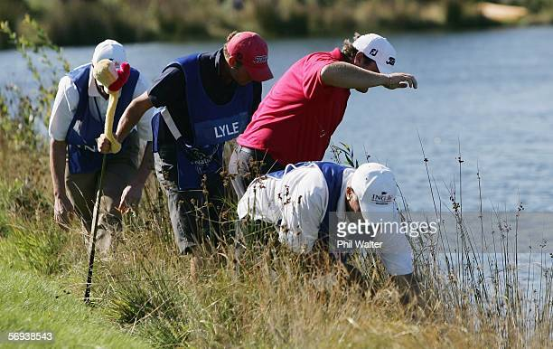 Jarrod Lyle of Australia looks for his ball on the edge of the lake after it landed in the water when he was tied for 1st place on the fourth day of...