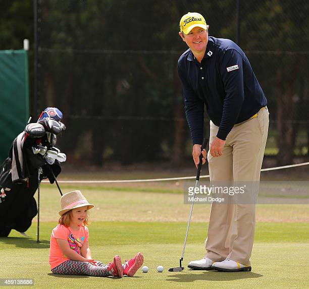 Jarrod Lyle of Australia putts on the practice green with daughter Lucy Lyle watching ahead of the 2014 Australian Masters at The Metropolitan Golf...