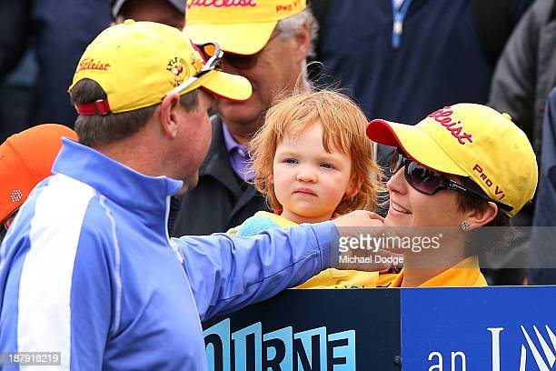 Jarrod Lyle of Australia touches his wife Briony Lyle on the chin who holds his daughter Lusi Lyle on the first tee before his shot during round one...