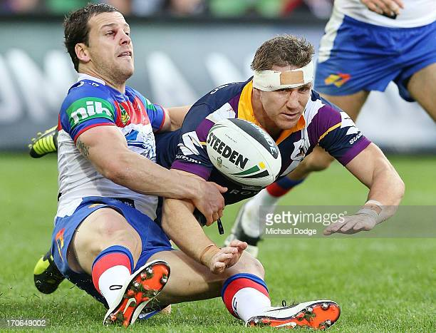 Jarrod Mullen of the Knights tackles Ryan Hoffman of the Storm during the round 14 NRL match between the Melbourne Storm and the Newcastle Knights at...