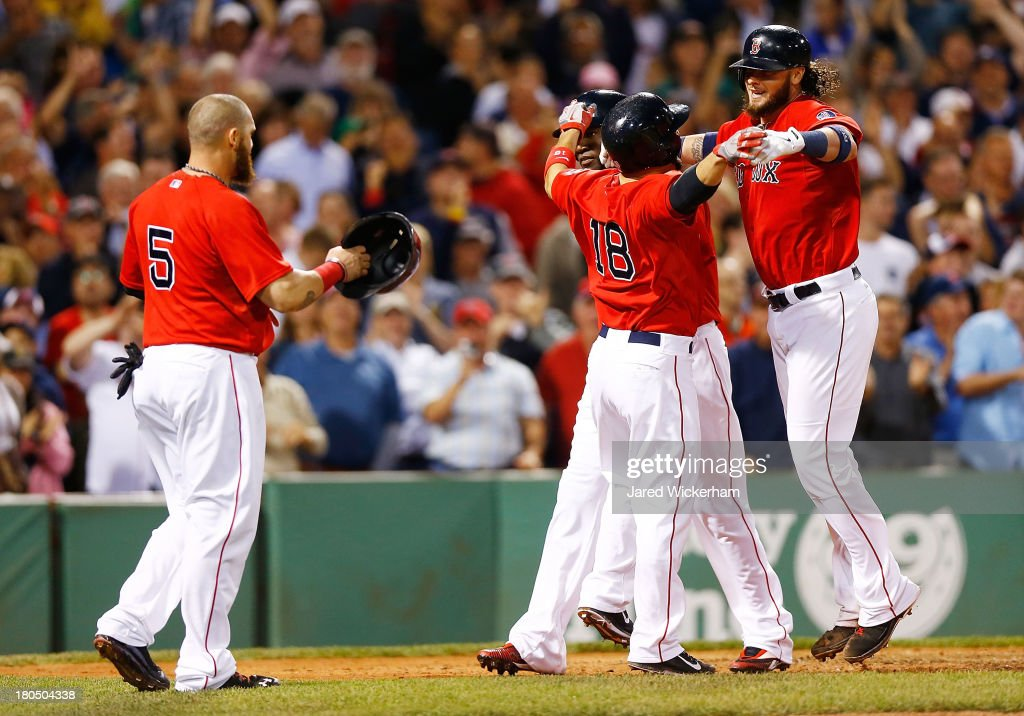 Jarrod Saltalamacchia #39 of the Boston Red Sox is congratulated by teammates at home plate including Shane Victorino #18, David Ortiz #34, and Jonny Gomes #5 of the Boston Red Sox after hitting a grand-slam home run in the 7th inning against the New York Yankees during the game on September 13, 2013 at Fenway Park in Boston, Massachusetts.