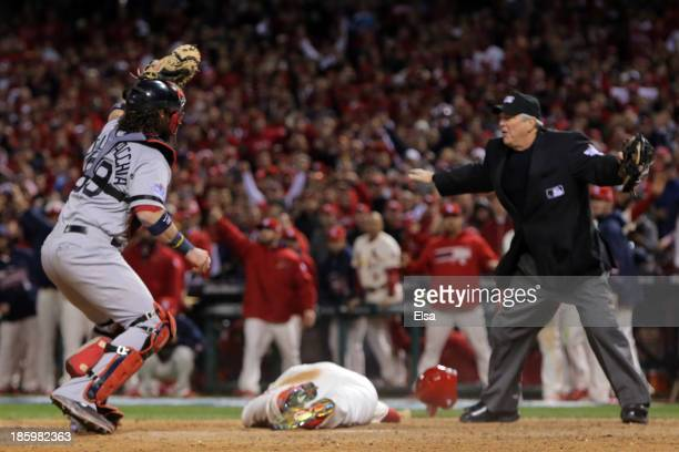 Jarrod Saltalamacchia of the Boston Red Sox reacts as Home Plate Umpire Dana DeMuth calls Allen Craig of the St Louis Cardinals safe at home in the...