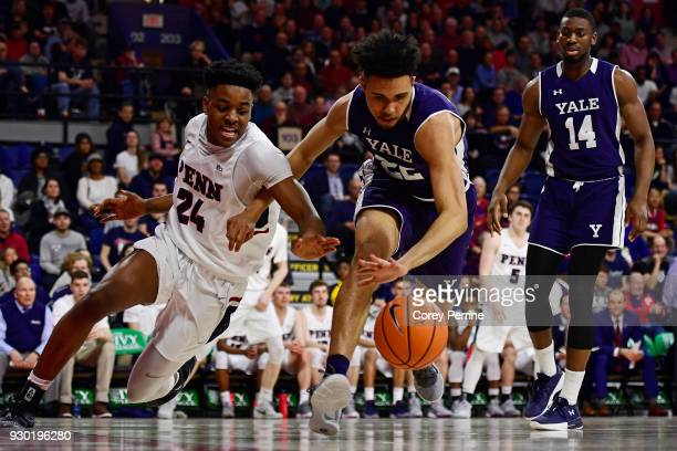 Jarrod Simmons of the Pennsylvania Quakers can't get the ball against Austin Williams as Jameel Alausa of the Yale Bulldogs looks on during the...