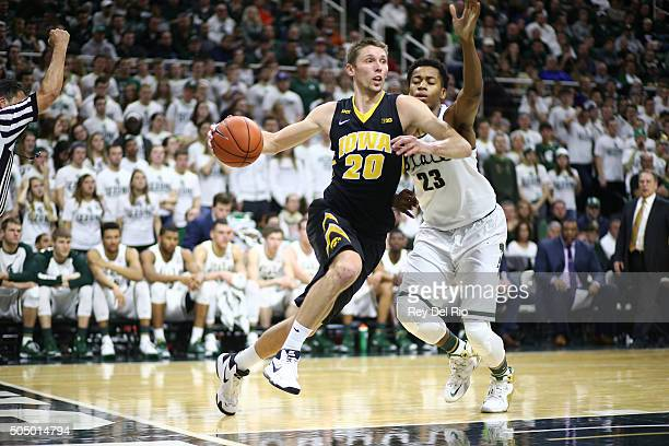 Jarrod Uthoff of the Iowa Hawkeyes drives to the basket and fouled by Deyonta Davis of the Michigan State Spartans in the first half at the Breslin...