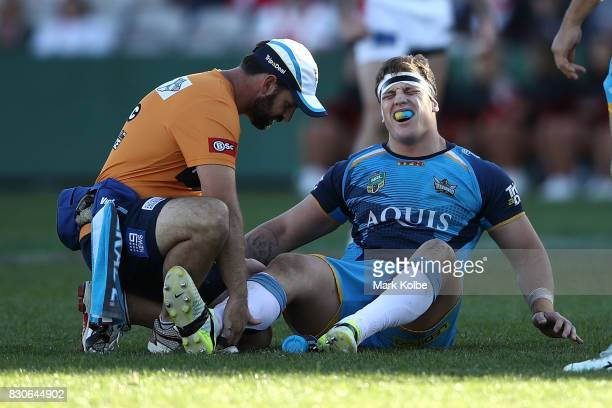 Jarrod Wallace of the Titans grimaces as he receives attention from the trainer during the round 23 NRL match between the St George Illawarra Dragons...