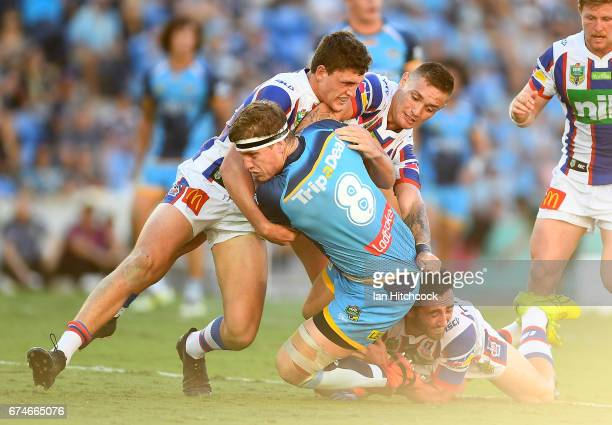 Jarrod Wallace of the Titans is wrapped up by the Knights defence during the round nine NRL match between the Gold Coast Titans and the Newcastle...