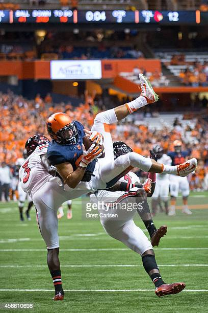 Jarrod West of the Syracuse Orange makes a long reception against James Sample and Charles Gaines of the Louisville Cardinals at the end of the...