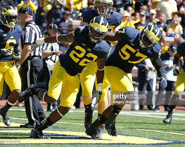 Jarrod Wilson of the Michigan Wolverines celebrates a fourth quarter interception in the end zone with Frank Clark while playing the Akron Zips at...